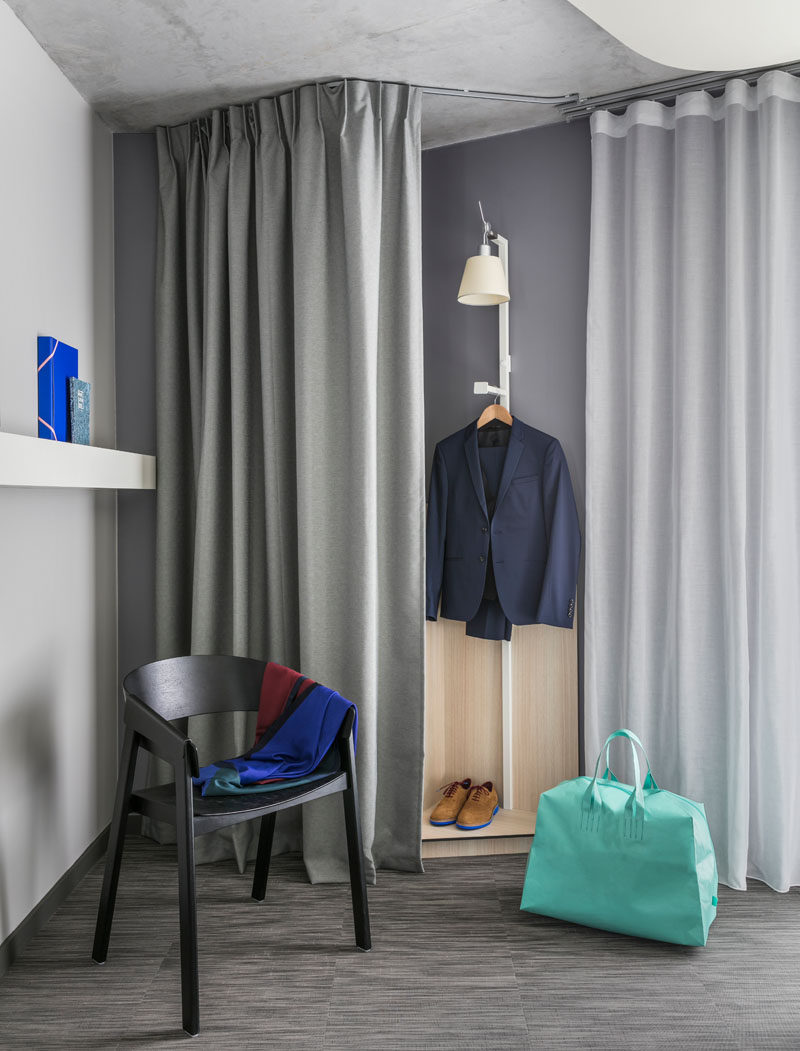 Curtains are used in this modern hotel room to hide a closet area.