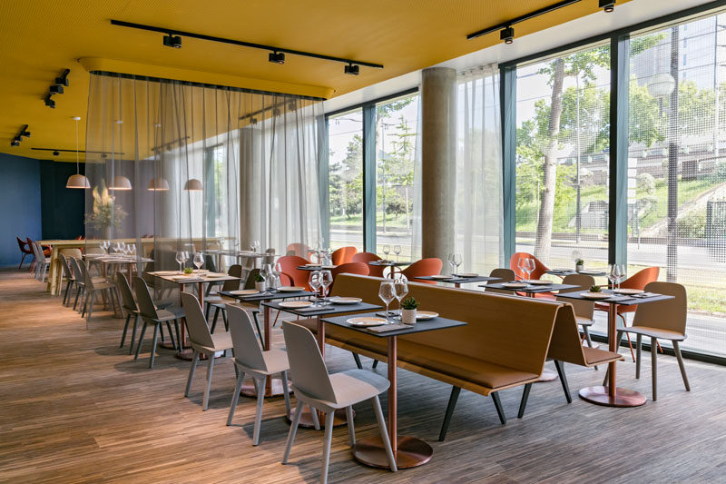 This modern hotel has an area set up for dining. Long bench seating sits back to back to create two rows of dining tables and chairs.
