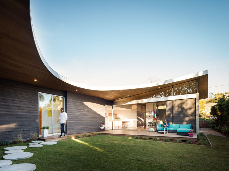 This modern and unique home has a curved roof, creating a U-shape floor plan.