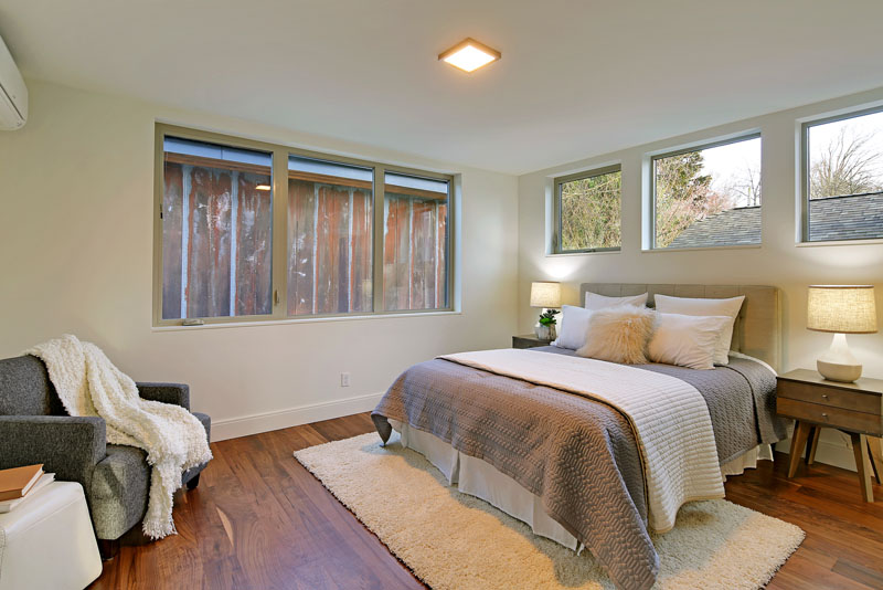 The bed in this modern bedroom sits underneath and beside windows, providing lots of light. Two wood nightstands with lamps compliment the walnut floor and colors used in the room.