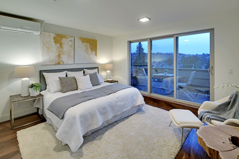 In this modern bedroom the bed sits beside a set of sliding glass doors that lead to a small balcony. A white plush area rug on the walnut floor gives the room a cozy feel.