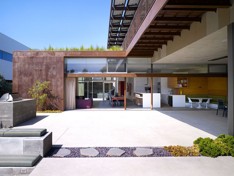 At the rear of this modern house, a large concrete patio is revealed with a 40 foot long glass sliding door that leads to the inside of the house.