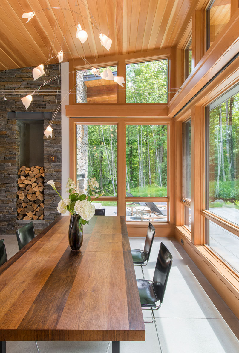 Wood framed windows provide this dining room views of the surrounding woods. A large wood table also compliments the wood ceiling and window frames.