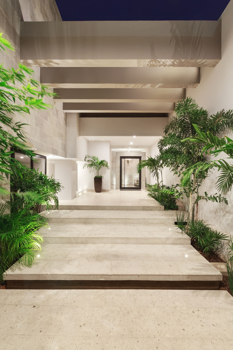 Located behind a grand iron door at the front of this modern house, is a narrow courtyard and entryway that provides the home owners more privacy from the street. Lush vegetation lines the pathway and existing concrete beams were renovated. At the end of the path is a large oversized glass door that allows for a glimpse inside.