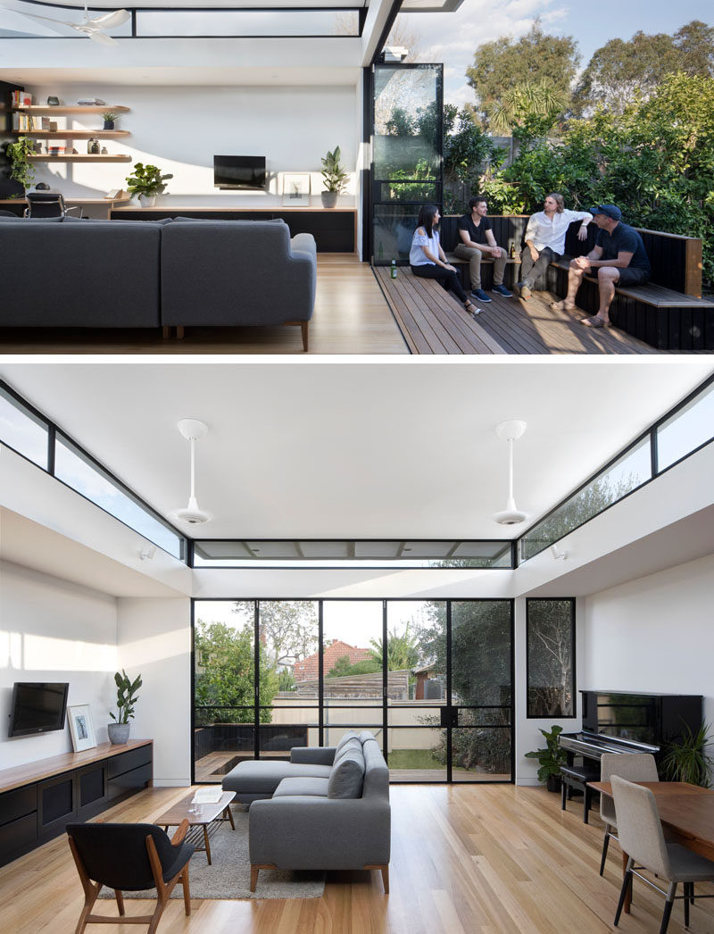 This modern house extension, which opens up to the backyard, has a wooden deck with built-in seating, with the stairs acting as an additional spot to sit. Folding black-framed doors can be closed at night, however they don't block the view of the garden as they are glass, and during the day, the sunlight can flood the interior.