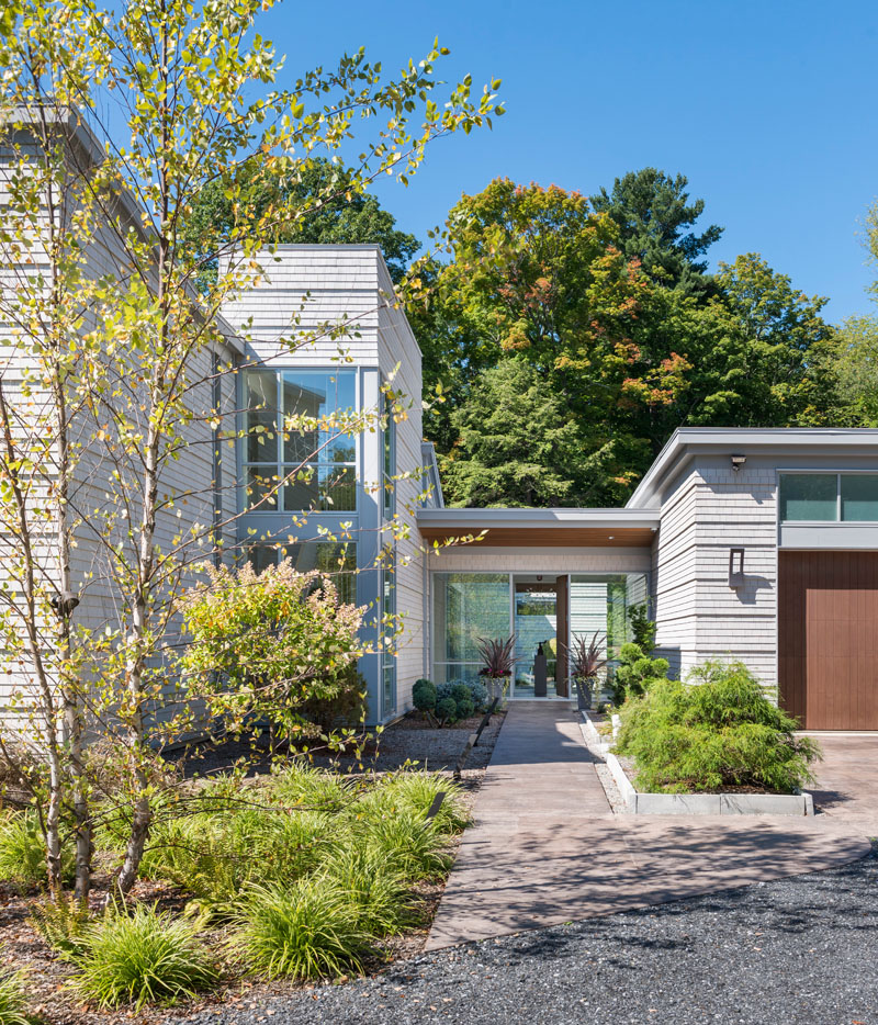 A landscaped path leads to the front entrance of this modern house, with the garage on the right and the house on the left. The home has been designed with a flat roof and floor to ceiling glass windows, allowing sunlight to fill the interior.