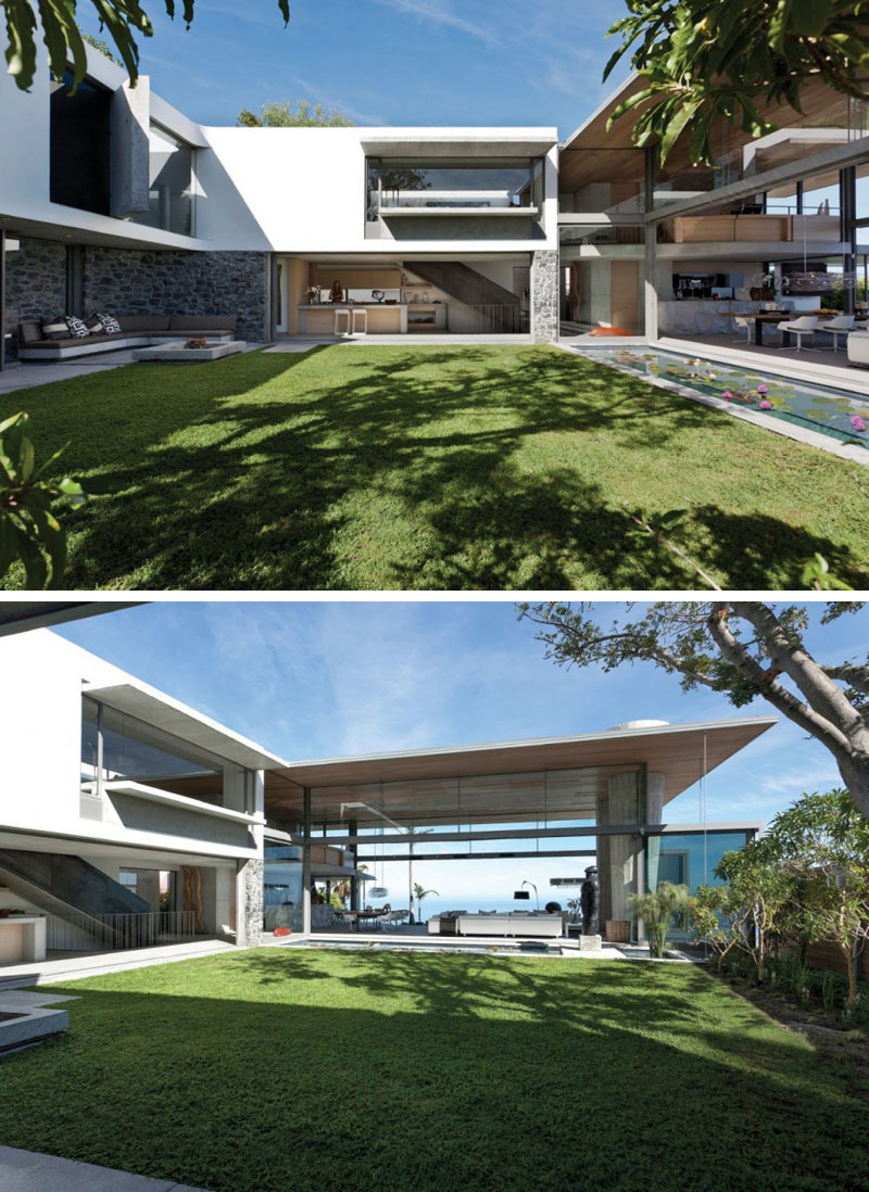 A central grassy courtyard is revealed that can lead into other areas of this modern house. To the side of the courtyard a long water feature is displayed.