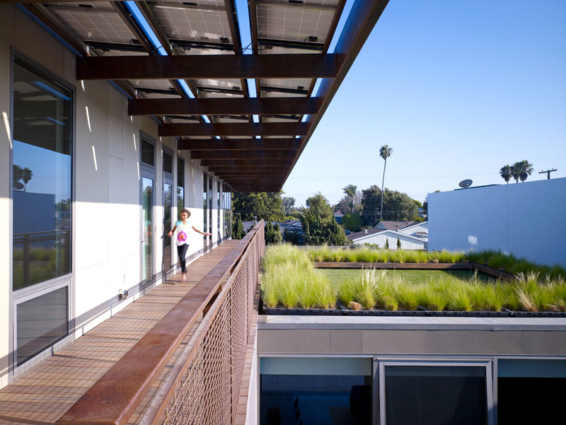 This modern long exterior walkway appears at the top of this house, leading to the bedrooms. A green roof has been added above the living room to provide environmental benefits.