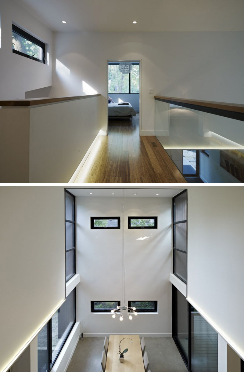 On the top floor a modern wood bridge with a glass safety railing leads to the master bedroom. Looking over the railing, one can see the dining area with the double-height ceiling.