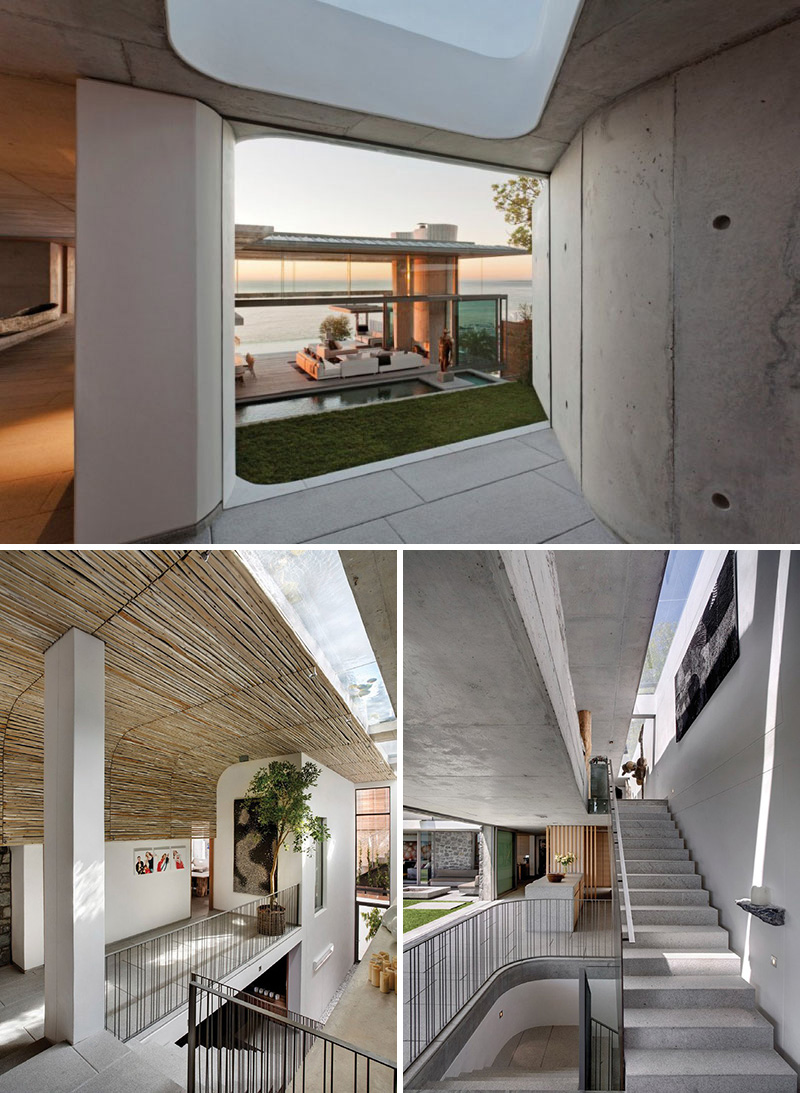 A modern concrete hallway brings you to a set of stairs that lead to the different levels of this house. A floor-to-ceiling window provides a glimpse of the courtyard below.