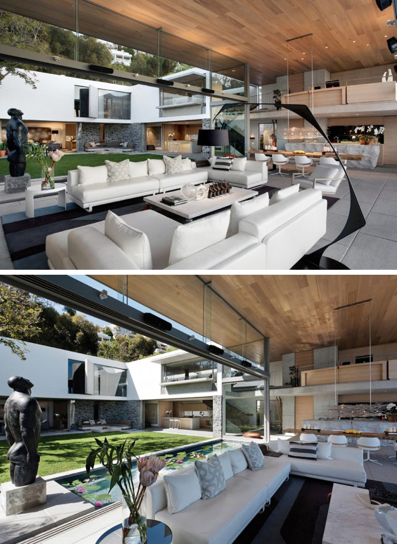 This modern living area is defined by white upholstered furniture that sits on a large black and grey area rug. To create continuity, the wood ceiling travels from the interior of the house through to the exterior.