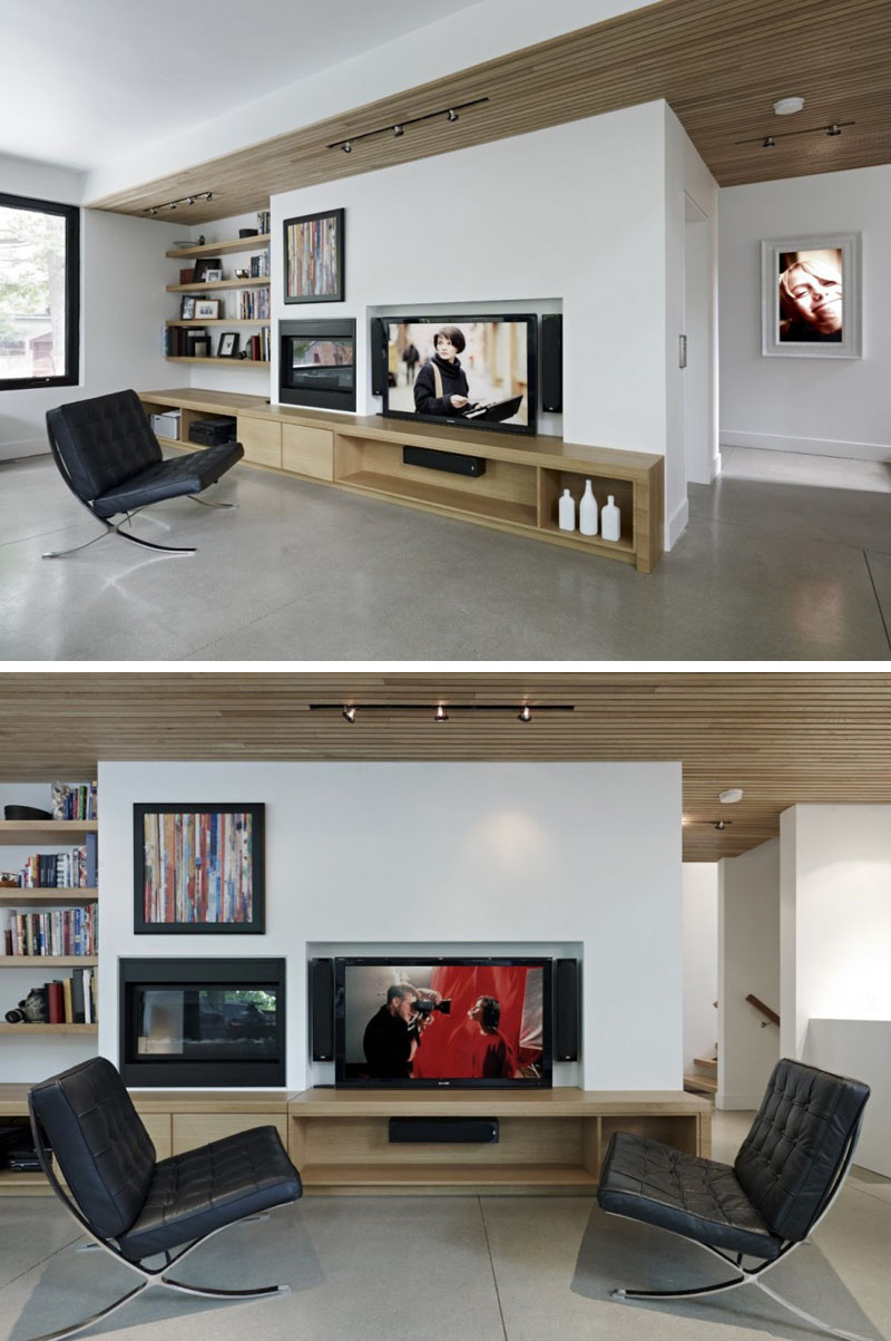 In this modern living room, built-in wood shelves, and entertainment unit compliment the wood used in ceiling. Behind the wall of the TV, is the elevator that leads to other parts of the home.