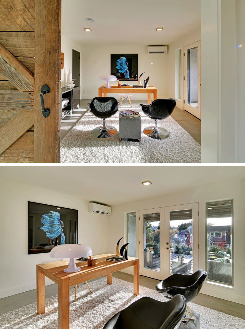 To the left of the entrance in this modern home, and through a sliding wood barn door is the home office. A set of glass, white framed doors lead to the outdoor patio by the front entrance