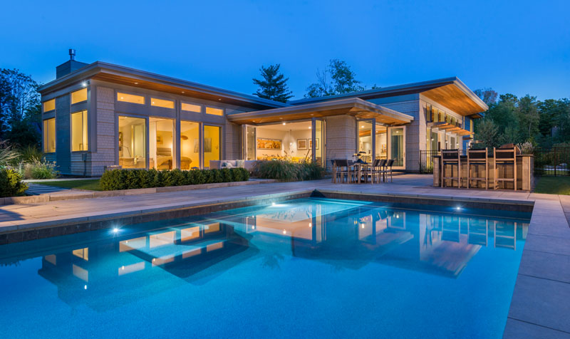 This modern house open up to a swimming pool, outdoor lounge, dining area and a bar.