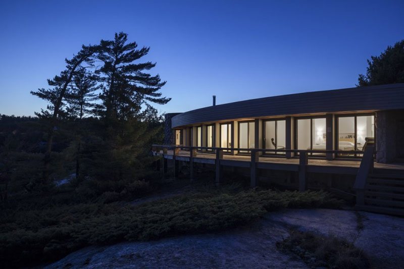 Altius Architecture have given this 1970's lakeside home, a modern house renovation in Parry Sound, Canada. A semi-circle floor plan with an open layout are used along with, clean white interiors and various lighting to keep the house light and airy.