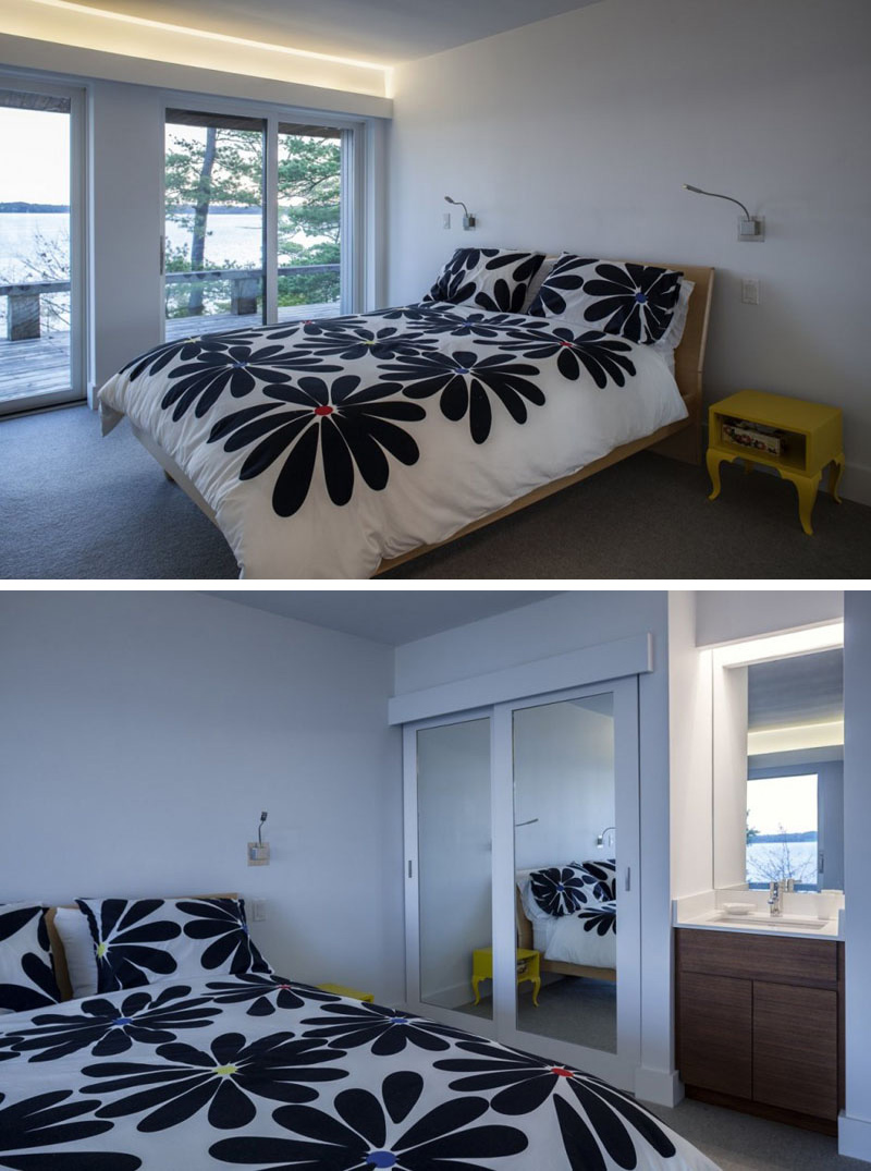 The large floral print blanket and yellow nightstand add a pop of color in this modern bedroom. A mirrored closet with sliding doors is placed beside a small sink with wood cabinets. Glass sliding doors with hidden lighting above lead to the wood balcony of the house.