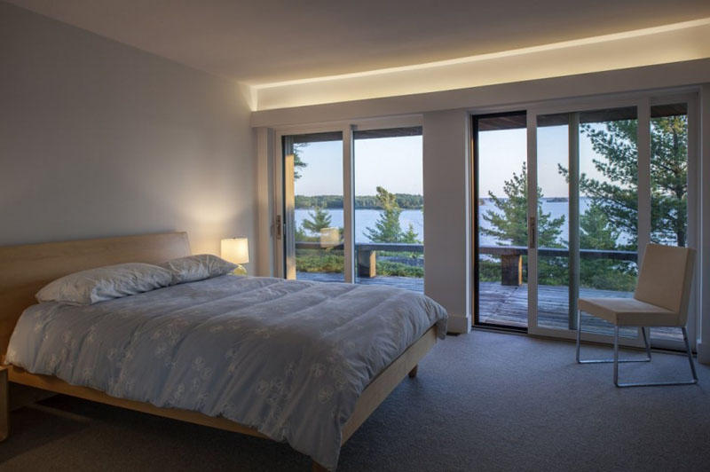 In this modern bedroom, a wood framed bed sits beside a set of glass sliding doors that lead to a balcony. Hidden lighting is used in this room above the balcony doors.