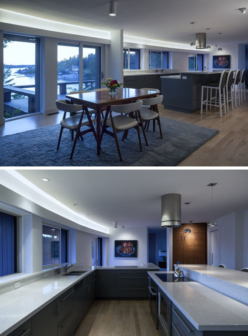 Hidden lighting above the windows and the glass balcony doors in this modern kitchen and dining area ensures that these rooms are always bright.