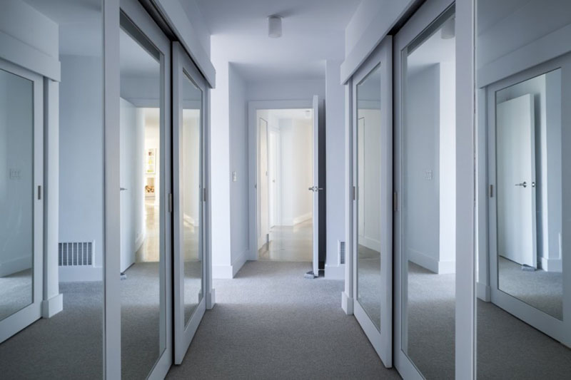 Leading to the sleeping quarters of this modern house is a hallway, and mirrored front closets guide you to the master bedroom.