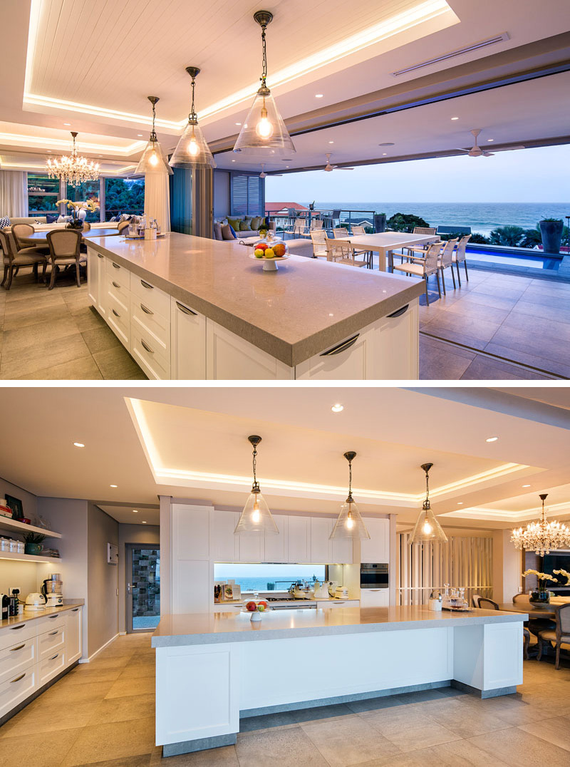 In this modern kitchen, a long white and grey island sits below three glass pendant lights that are hung from a recessed ceiling with hidden lighting. The kitchen faces the pool and views the expansive ocean.