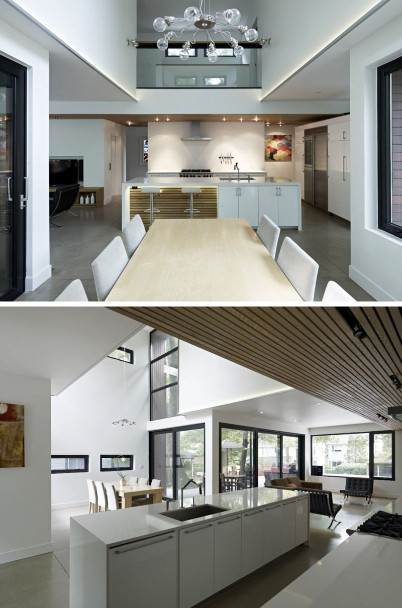 In this modern dining room, a unique chandelier with exposed bulbs hangs above the long wood dining table. The surrounding windows in this double height room make the space light and airy.