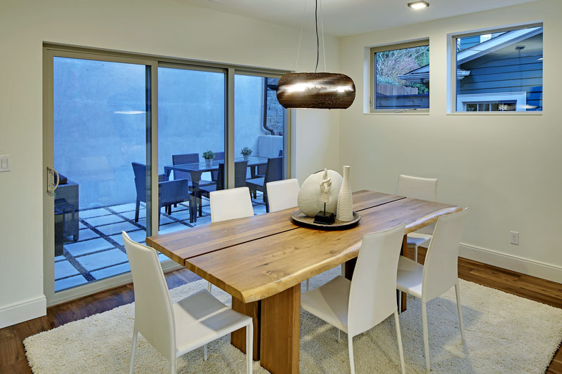 In this modern dining room, a wood table sits on a white area rug and is surrounded by white chairs. A handmade pendant light hangs above the table that compliments others through the home.