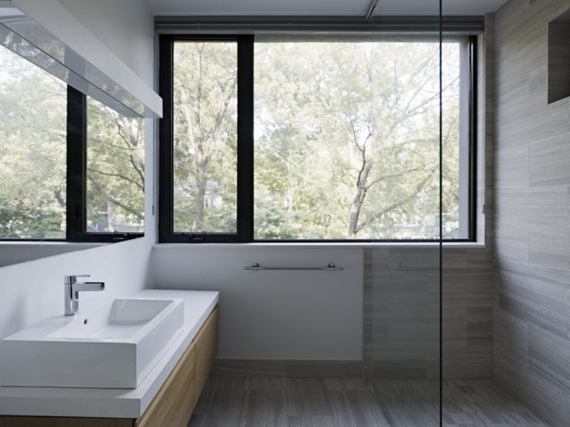 In this modern bathroom, a glass surround shower is placed beside a large black framed window providing a view of outside. A wood vanity with white counter and sink adds extra storage to the bathroom.