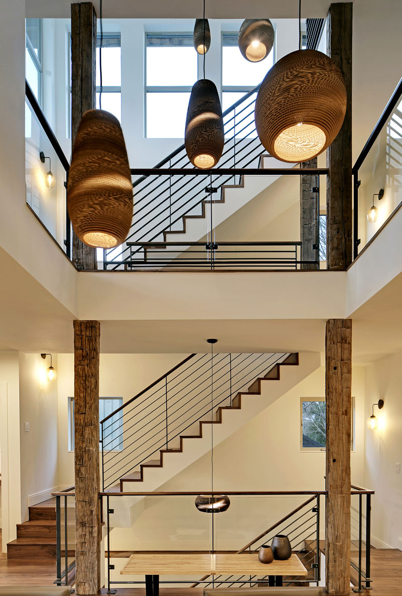 The four-storey set of stairs is situated beside an atrium in the middle of this modern home. Long, handmade pendant lights hang in the atrium filling the big open space.