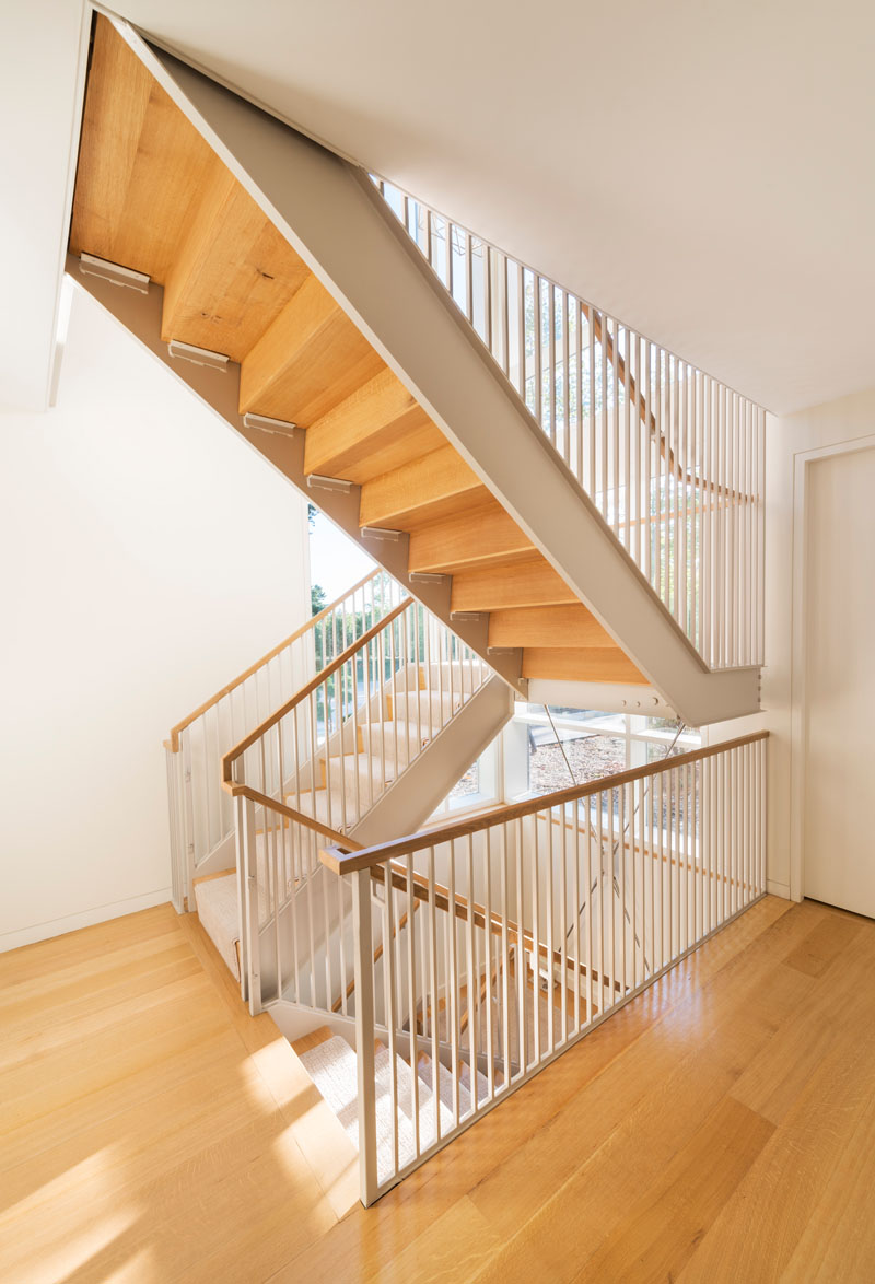 This modern staircase with wooden treads connect the various levels of the home. A light carpet that matches the walls has been used on the stairs.