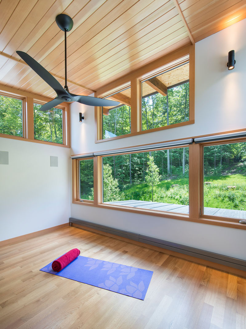 This modern house surrounded by woods, has a yoga studio with high ceilings and views of the trees.