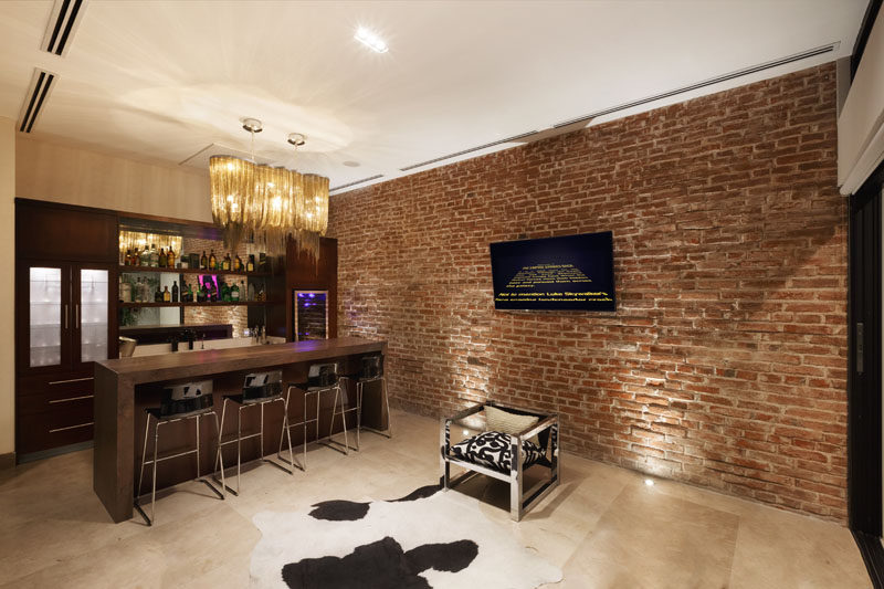 This modern home bar features a brick wall with accent lights, that adds to texture to the space, and a custom-built bar lines the wall. A chrome chair that was part of the original house furnishings was rescued and included with the new furnishings.