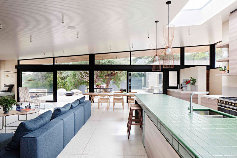 This modern house has a large main living area that's home to the living room, dining room and kitchen. A sloped roof and skylights add plenty of natural light to the room.