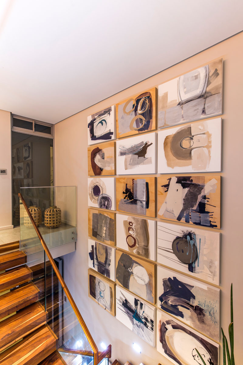 This set of modern wood stairs leads down from the dining room into the entertainment areas of the house. Decorative art pieces fill the wall that leads downstairs.