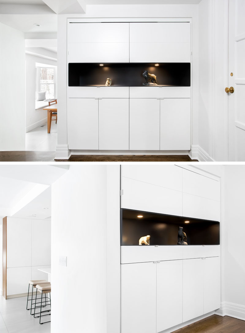 This entryway has been updated with a wall of white cabinets, with the middle section painted black to create a dramatic backdrop for highlighted artworks.