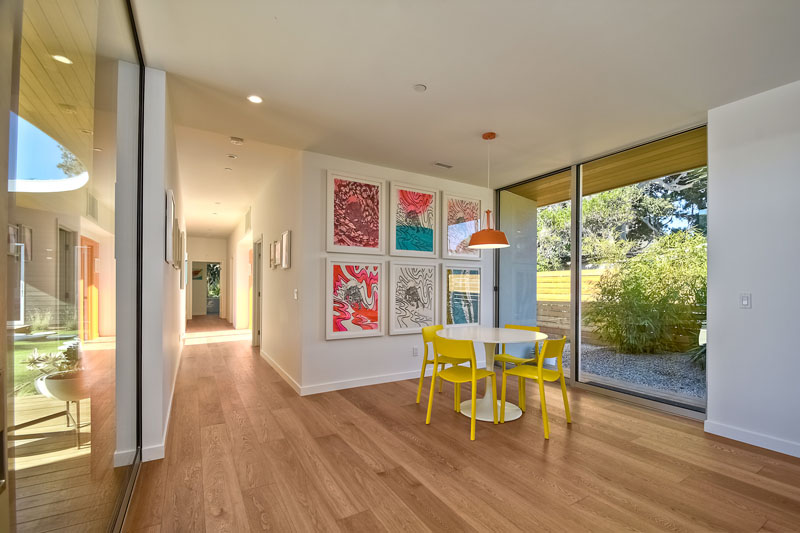 In this modern breakfast nook, a white table with yellow chairs, sits below a bright orange pendant lamp. A sliding glass door provides easy access to outside.