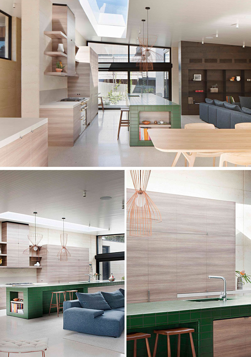 In this modern kitchen, a large, green tiled island adds a pop of color and helps to connect the landscaping with the interiors. Light wood cabinets run along the wall with open shelves flanking each side of the exhaust fan.