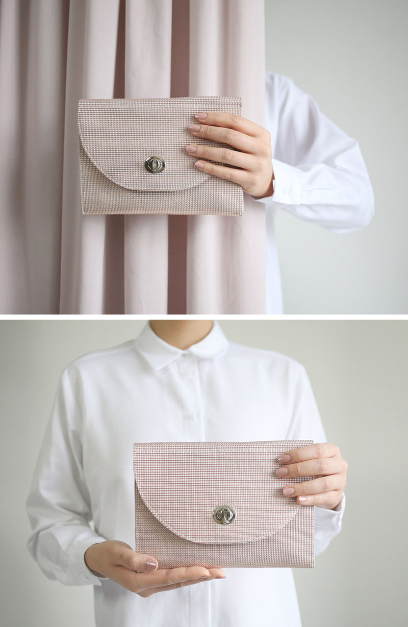 This modern leather clutch is blush in color with a textured material.