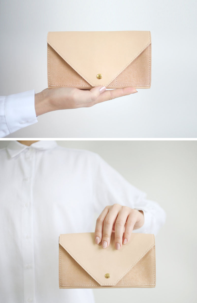This modern beige leather hand clutch has textured detail and a gold button snap.