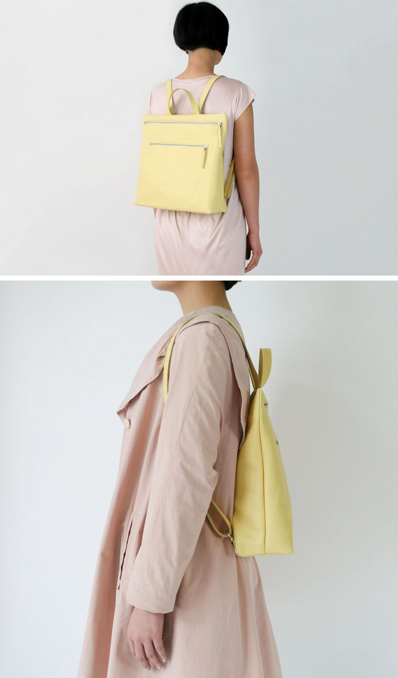 This modern yellow leather backpack has two large silver zippers, and a handle at the top.