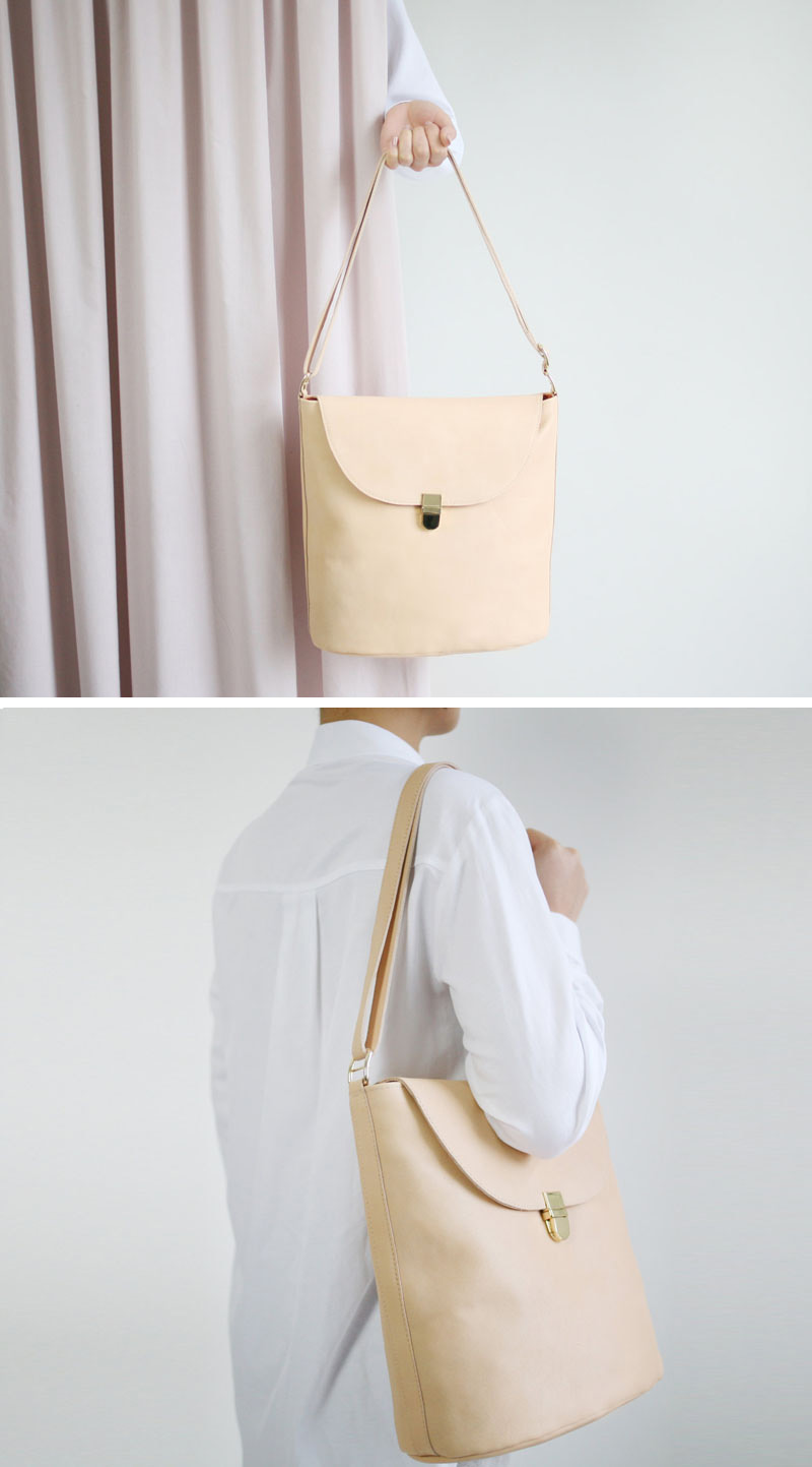 This modern yellow leather shoulder bag has a gold buckle in the front, and is large and modern in design