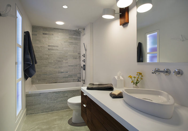 In this simple and modern bathroom, light grey rectangular tiles have been used in the bath/shower, while a triangular-shaped white sink sits on the on a dark wood vanity.