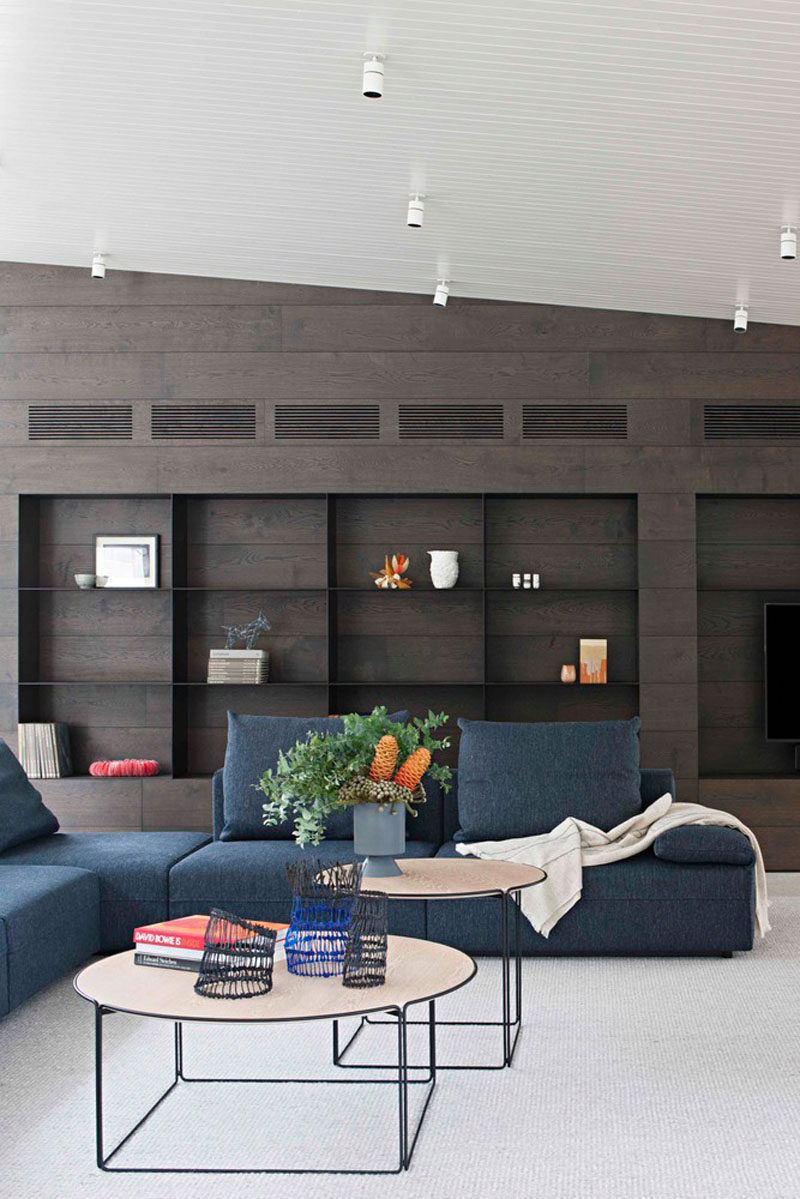 This modern living room has a light colored concrete floor, a dark blue couch and a large black bookshelf with dark wood.