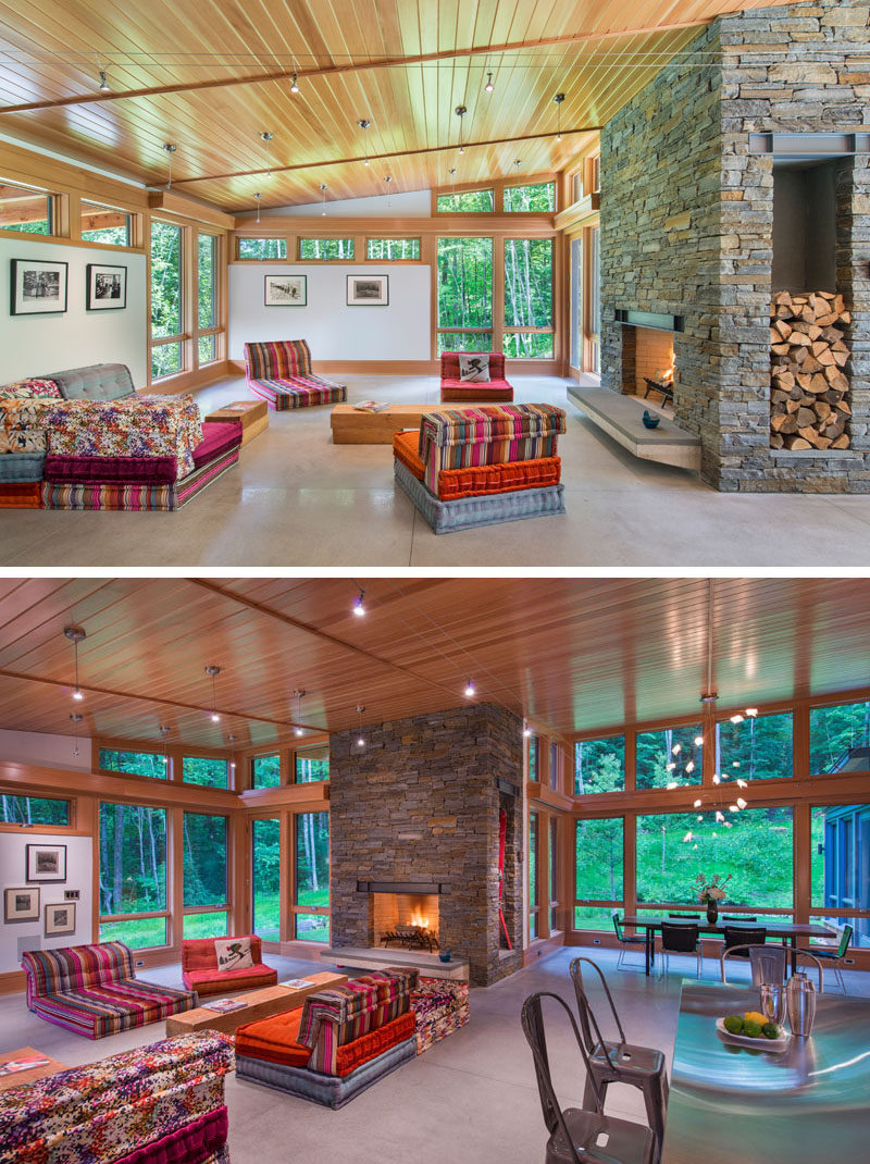 In this modern living room, bright colored seating and a fireplace with a stone surround creates a relaxing environment. Natural light floods the interior through the numerous windows, some of which have been designed to follow the roof line.