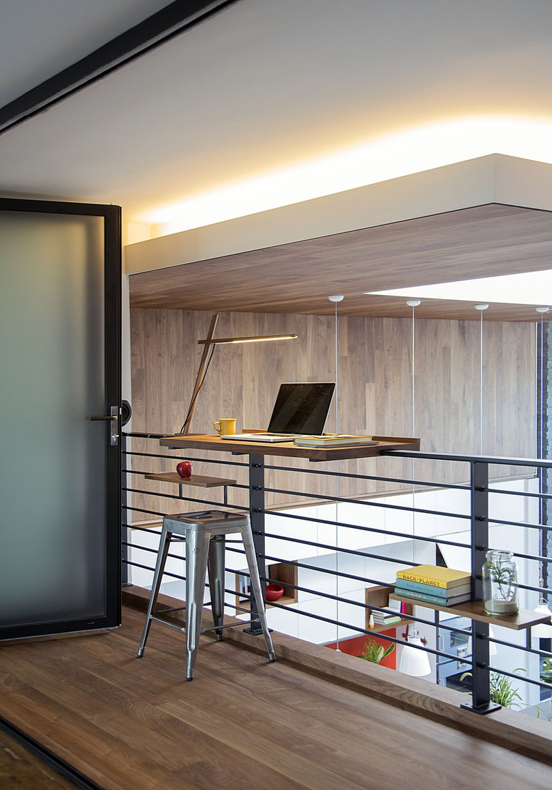 A wood desk has been attached to a black railing to create a work space that can easily view the lower level of this modern loft. Hidden lighting in the ceiling provides an extra glow to this modern lofted level.