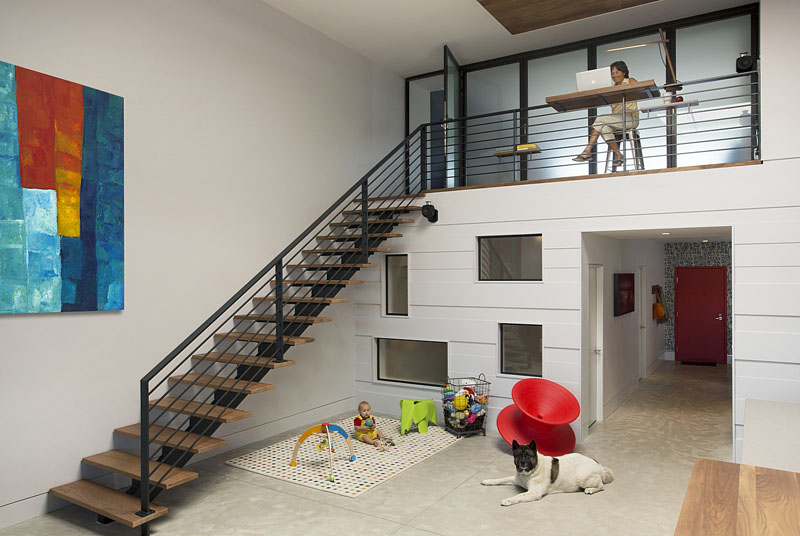 In this modern loft, walnut wood stairs with a black hand railing lead to the lofted part of the home. Underneath the stairs, a small area has been set up as a play area, and you can see the windows that look into the nursery.