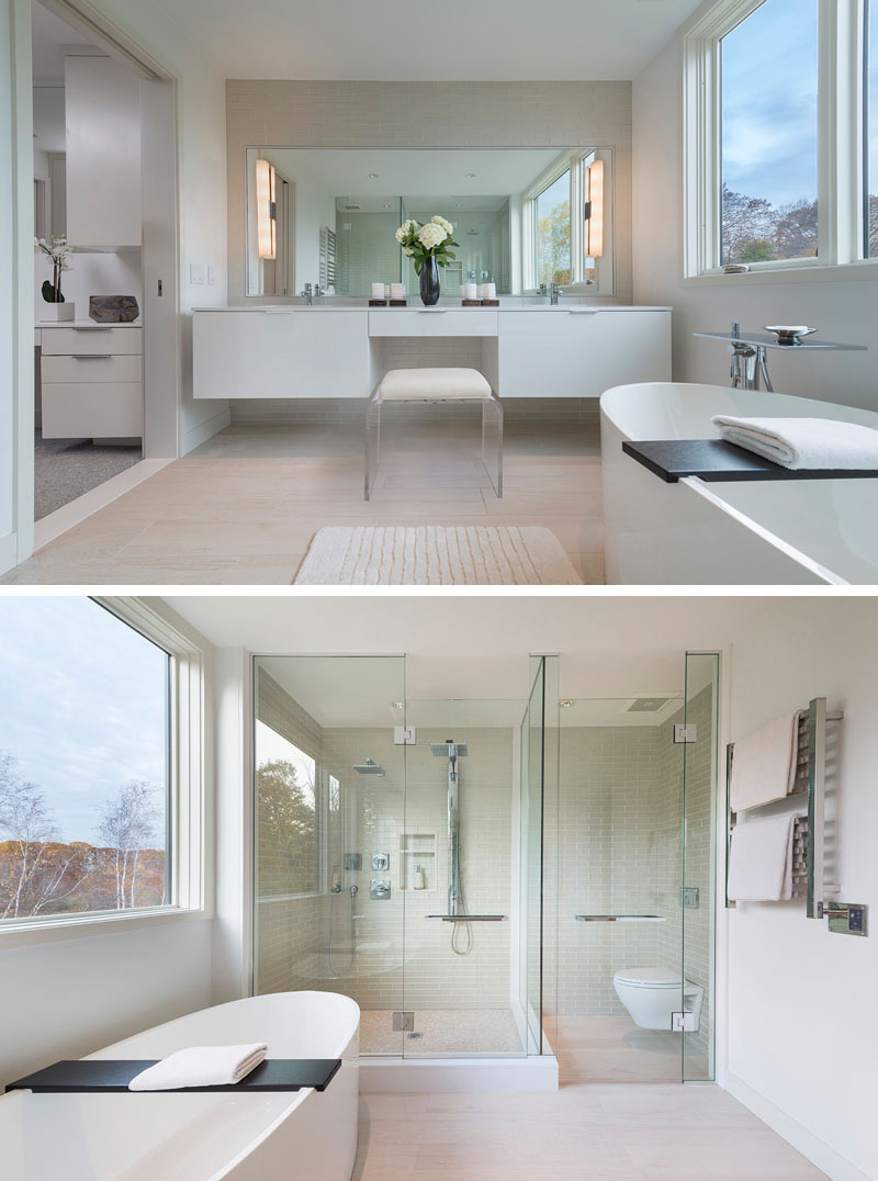 In this modern master bathroom, a large rectangular mirror above the white counter has long opaque lights attached to either side. The glass surround shower is placed beside the toilet which is also surrounded by glass.