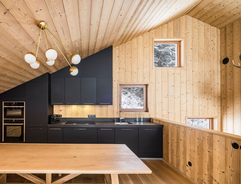 At the top of the stairs in this modern mountain house is the kitchen. Matte black kitchen cabinets fill the wall and follow the sloped roof line.