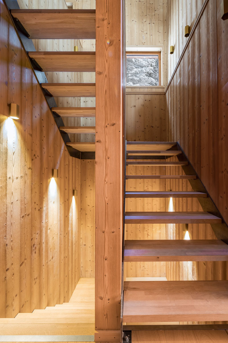 This modern mountain house has wood stairs that connect the various levels of the home, while wall sconces and square windows allow light to fill the stairwell.