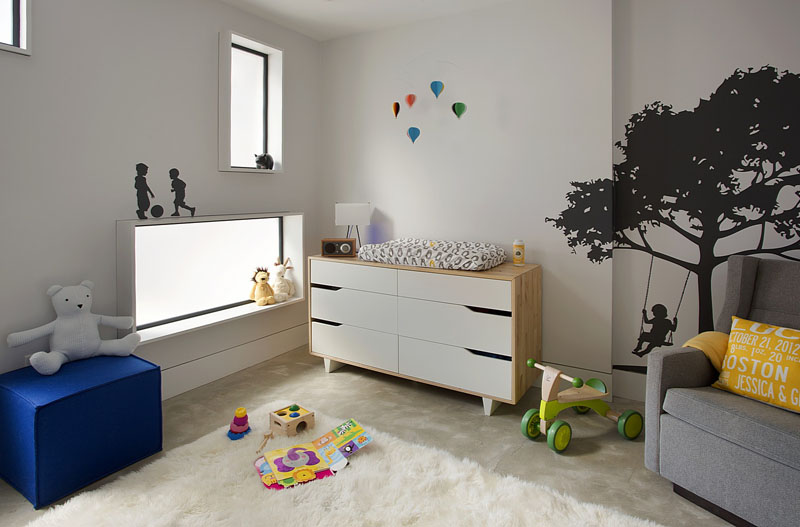 In this modern nursery, rectangular opaque windows glow from the light in the living area, while wall decals of children playing add a touch of fun to the room.