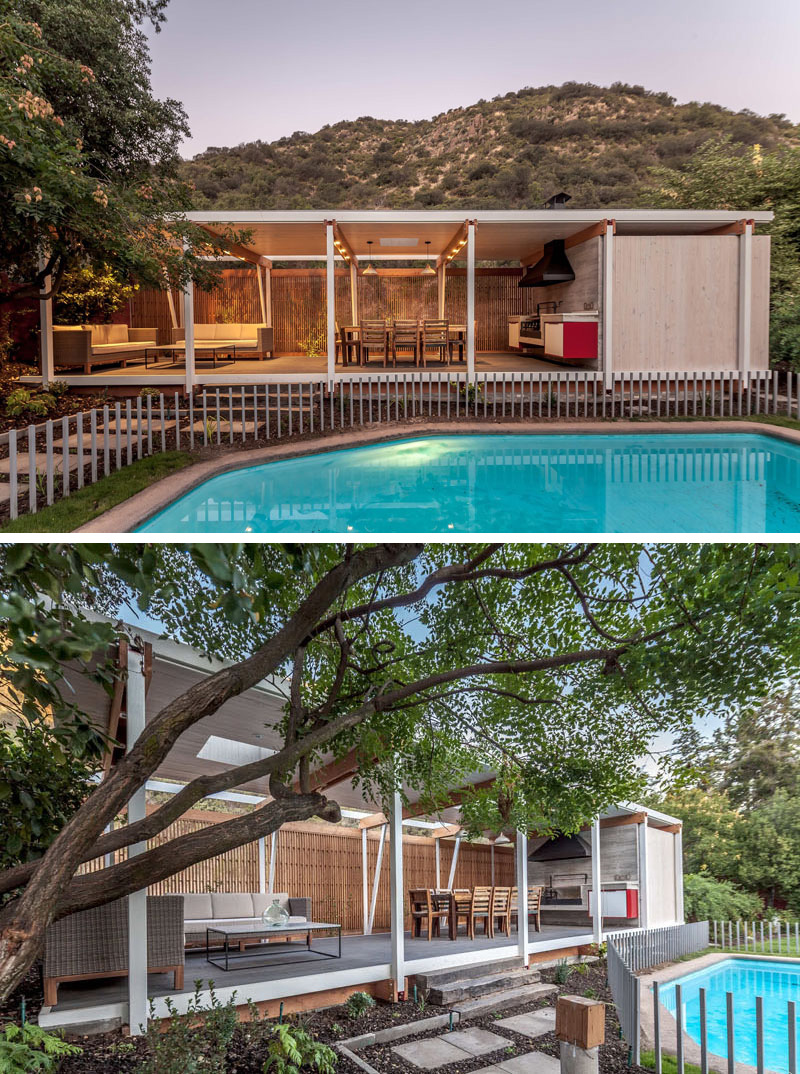 Slightly raised from the ground, this modern pool house with steel white pillars provides a mostly unobstructed view of the gated outdoor pool.